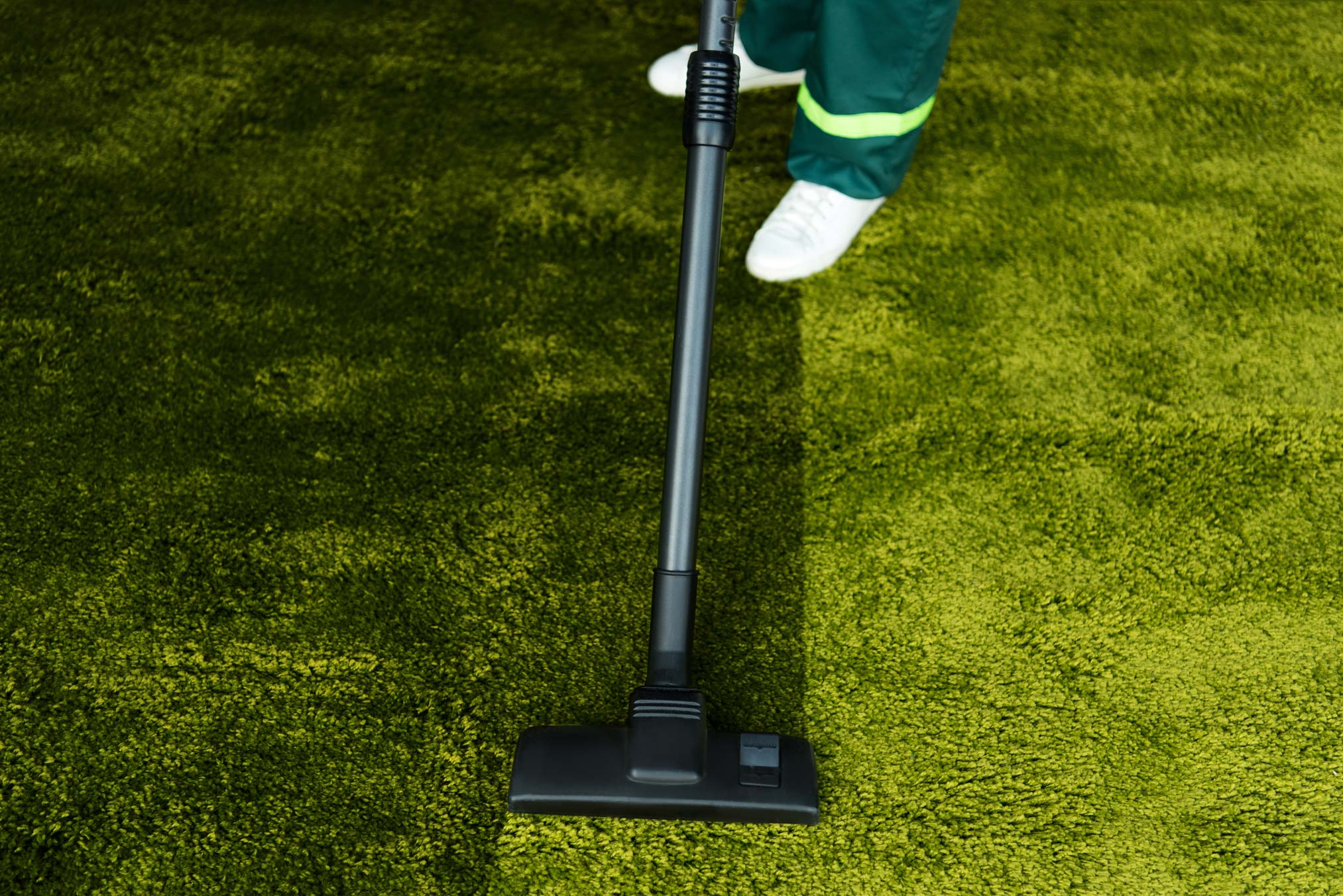 low-section-of-person-cleaning-green-carpet-with-v-QKZLDNG